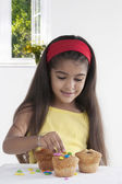 Girl decorating muffins — Stock Photo