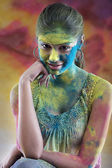 Woman's face covered in holi colours — Stock Photo