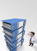 Businessman tensed after looking at a stack of files — Stockfoto