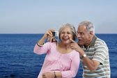 Couple looking at photographs in a camera — Stock Photo