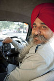 Sikh taxi driver standing next to his vehicle — Stock Photo