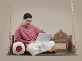 South Indian man with a laptop — Stock Photo
