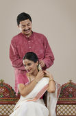 Man tying a Gajra on his wife's hair — Stock Photo