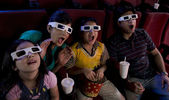 Family watching a movie with 3D glasses — Stock Photo