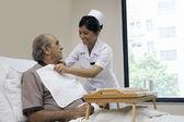 Pielęgniarka pomoc pacjentowi jeść — Zdjęcie stockowe