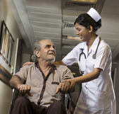 Nurse helping a patient on a wheelchair — Stock fotografie