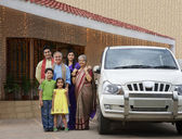 Family standing next to a car — Stock Photo