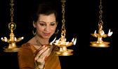 Woman lighting diyas — Stock Photo
