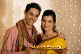 Couple holding a tray of diyas — Stock Photo
