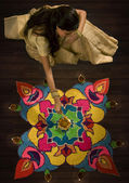 Woman sitting next to a rangoli — Stock Photo