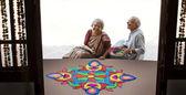 Old couple making a rangoli — Stock Photo