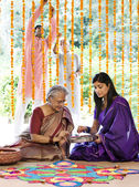 Mother and daughter making a rangoli — Stock Photo