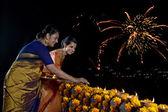 Mother and daughter lighting diyas — Stock Photo