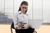 Secretary with a credit card and laptop — Stock Photo