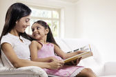 Mother and daughter with a story book — Stock Photo
