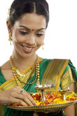 Portrait of a woman holding a tray with diyas — Stock Photo