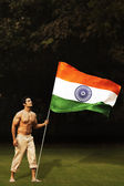 Bare chested man running with the Indian flag — Stock Photo