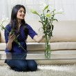Young woman arranging flowers in a vase — Stock Photo