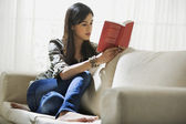 Young woman with a book on a sofa — Stock Photo