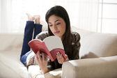 Junge Frau mit einem Buch auf dem sofa — Stockfoto