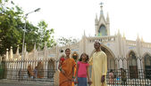 Family standing in front of a church — Stock Photo