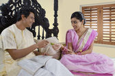 Bengali couple relaxing on a bed — Stock Photo