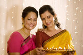 Mother and daughter holding a tray of diyas — Stock Photo