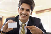 Businessman holding a business card — Stock Photo
