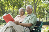 Old couple reading in park — Stock Photo