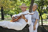 Old man plays on guitar for woman — Stock Photo