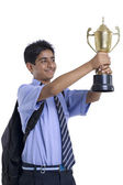 Teenage boy holding winning trophy — Stock Photo