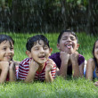 Happy boys and girls catching raindrops on tongue — Stock Photo #46040177