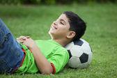 Teenage boy with soccer ball lying on grass — Stock Photo