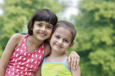 Smiling girls hugging each other — Stock Photo