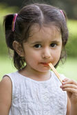 Cute girl licking candy stick — Stock Photo