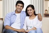 Young couple sitting on sofa — Stock Photo