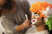 Make up artist applying make up to clown — Stock Photo