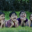 Happy boys and girls catching raindrops on tongue — Stock Photo #46427291