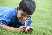 Boy using magnifying glass — Stock Photo