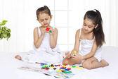 Children playing while sitting on bed — Stock Photo