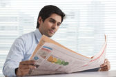 Businessman thinking with newspaper — Stockfoto