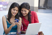 Young women using cell phone — Stock Photo