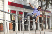 Man jumping over railings — Stock Photo