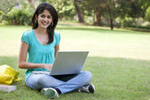 Young college student using laptop — Stock Photo