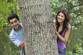 Smiling college students behind tree — Stock Photo