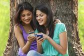 Genç kadınlar cep telefonlarını kullanarak — Stok fotoğraf