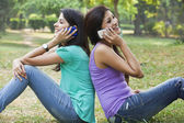 Young women using cell phones — Stock Photo