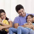 Happy family sitting on sofa — Stock Photo #46455575