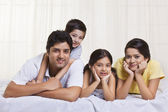 Smiling family lying in bed — Stock Photo