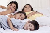 Family sleeping on bed — Stock Photo